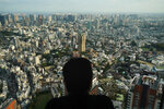A man watches the cityscape of Tokyo from an observation deck located on the top floor of Roppongi Hills Mori Tower, Thursday, Sept. 19, 2019, in Tokyo. (AP Photo/Jae C. Hong)