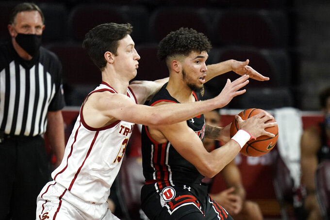 Southern California's Drew Peterson, left, pressures Utah's Timmy Allen during the second half of an NCAA college basketball game, Saturday, Jan. 2, 2021, in Los Angeles. USC won 64-46. (AP Photo/Jae C. Hong)