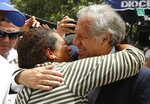 Organization of American States Secretary-General Luis Almagro, right, embraces a Venezuelan migrant at the