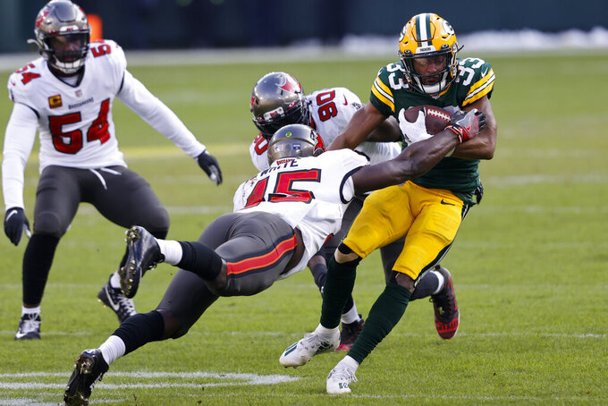 Tampa Bay Buccaneers' Devin White (45) makes a leaping tackle on Green Bay Packers' Aaron Jones (33) during the first half of the NFC championship NFL football game in Green Bay, Wis., Sunday, Jan. 24, 2021. (AP Photo/Jeffrey Phelps)