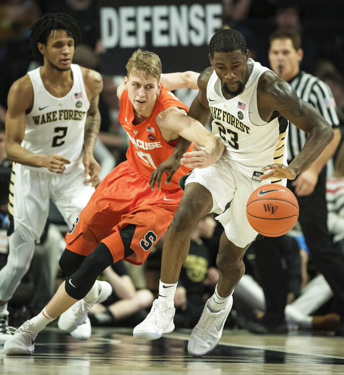 Wake Forest guard Chaundee Brown (23) takes the ball up the court while pressured by Syracuse forward Marek Dolezaj (21) during the second half of an NCAA college basketball game, Saturday, March 2, 2019, at Joel Coliseum in Winston-Salem, N.C. (Allison Lee Isley/The Winston-Salem Journal via AP)