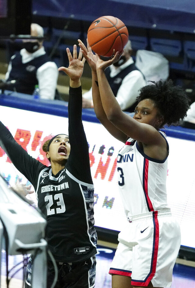 Connecticut guard Christyn Williams (13) shoots against Georgetown guard Milan Bolden-Morris (23) in the first half of an NCAA college basketball game Saturday, Jan. 23, 2021, in Storrs, Conn. (David Butler II/Pool Photo via AP)