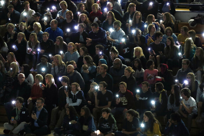 Attendees illuminate their mobile telephones during a community vigil to honor the victims and survivors of yesterday's fatal shooting at the STEM School Highlands Ranch, late Wednesday, May 8, 2019, in Highlands Ranch, Colo. (AP Photo/David Zalubowski)
