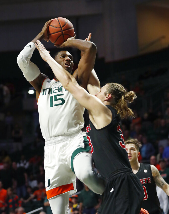 Miami center Ebuka Izundu (15) goes up for a shot against North Carolina State forward Wyatt Walker (33) during the first half of an NCAA college basketball game, Thursday, Jan. 3, 2019, in Coral Gables, Fla. (AP Photo/Wilfredo Lee)
