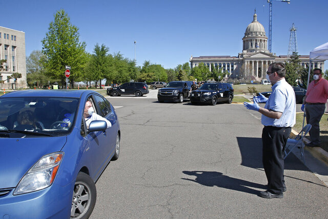 Paul Ziriax, right, Secretary of the Oklahoma State Election Board, wears a mask and gloves and practices social distancing due to COVID-19 concerns as people drive-thru a registration area for candidate filing outside the state Capitol Wednesday, April 8, 2020, in Oklahoma City. The new coronavirus causes mild or moderate symptoms for most people, but for some, especially older adults and people with existing health problems, it can cause more severe illness or death. (AP Photo/Sue Ogrocki)