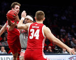 New Mexico guard JJ Caldwell (11) drives while defended by Wisconsin forward Nate Reuvers (35) and guard Brad Davison (34) in the second half of an NCAA college basketball game in the Legends Classic, Tuesday, Nov. 26, 2019, in New York. New Mexico defeated Wisconsin 59-50. (AP Photo/Kathy Willens)
