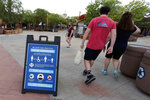 In this Wednesday, June 3, 2020 photo, signs about social distancing and other protocols are seen about the theme park as guests walk by at Universal Orlando Resort Wednesday, June 3, 2020, in Orlando, Fla. The theme park has reopened for season pass holders and will open to the general public on Friday, June 5. (AP Photo/John Raoux)