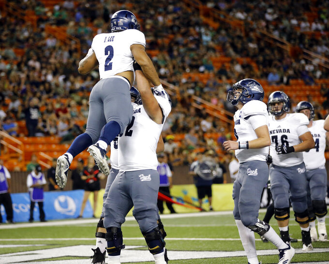 Nevada running back Devonte Lee (2) gets lifted in the air by offensive lineman Anthony Palomares (62) after Lee scored a touchdown against Hawaii during the second quarter of an NCAA college football game, Saturday, Oct. 20, 2018, in Honolulu. (AP Photo/Marco Garcia)