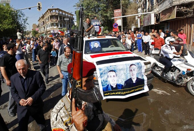 "File - In this Tuesday, Nov. 2, 2010 file photo, the coffins of two slain priests and their parishioners arrive at a funeral mass in Baghdad, Iraq. The victims were killed Sunday when gunmen stormed a church during mass and took the entire congregation hostage. The attack, claimed by an al-Qaida-linked organization, was the deadliest recorded against Iraq's Christians since the 2003 U.S.-led invasion unleashed a wave of violence against them. The text on the banner, in Arabic, reads ""Please, God, give him eternal rest and make your light shine on him."" (AP Photo/Hadi Mizban, File)"