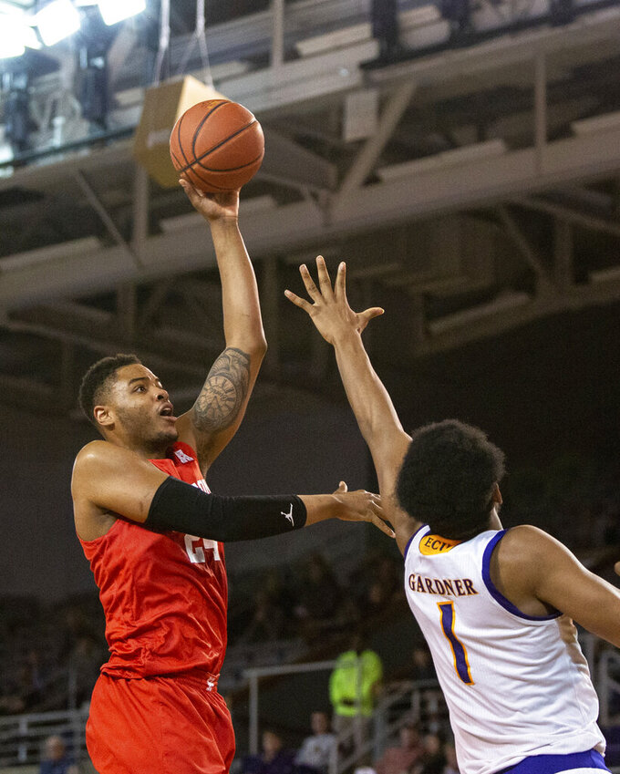 Houston's Breaon Brady, left, attempts a shot over East Carolina's Jayden Gardner, right, during the second half of an NCAA college basketball game in Greenville, N.C., Wednesday, Feb. 27, 2019. (AP Photo/Ben McKeown)