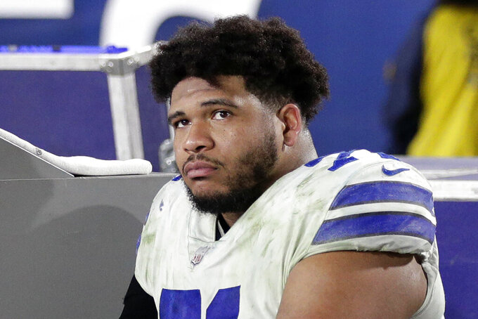 FILE - In this Jan. 12, 2019, file photo, Dallas Cowboys tackle La'el Collins sits on the bench during the second half in an NFL divisional football playoff game against the Los Angeles Rams, in Los Angeles. The Dallas Cowboys and right tackle La'el Collins have agreed on a new contract, the second extension to get settled during star running back Ezekiel Elliott's holdout. The deal signed Tuesday, Sept. 2, 2019, is the second extension Collins and the Cowboys have negotiated since he chose them as an undrafted free agent in 2015. (AP Photo/Jae C. Hong, File)