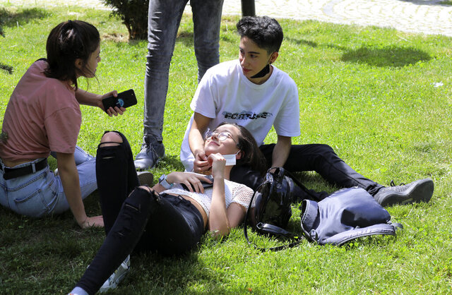 Turkish teenagers sit in popular Kugulu public garden amid the new coronavirus, in Ankara, Turkey, Friday, May 15, 2020. Teenagers were able to leave their homes for the first time in 42 days on Friday, as their turn came for a few hours of respite from Turkey's coronavirus lockdowns. Turkey has subjected people aged 65 and over and those younger than 20, to a curfew for the past several weeks.(AP Photo/Burhan Ozbilici)
