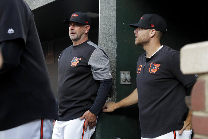 Baltimore Orioles manager Brandon Hyde, left, talks with Chris Davis in the dugout during the first inning of a baseball game against the Houston Astros, Friday, Aug. 9, 2019, in Baltimore. Davis said he reached a