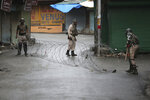 FILE - In this Saturday, Aug. 10, 2019, file photo, Indian paramilitary soldiers close a street using barbwire in Srinagar, Indian controlled Kashmir. Prime Minister Narendra Modi's Hindu nationalist-led government presented an order in parliament Aug. 5 revoking the autonomy of India's only Muslim-majority state, followed by a bill to split Jammu and Kashmir into two federal territories. On the eve of imposing this big political change, India shut down internet, phones and cable TV in the disputed region home to 12.5 million people. Officials have filled the void by circulating their own images and asserting the changes have widespread acceptance. But that portrayal hasn't stood up to scrutiny, with independent news reports suggesting otherwise. (AP Photo/Mukhtar Khan, File)