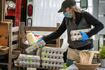 In this Thursday, May 28, 2020 photo, Beth Shiller of Dandelion Spring Farm stacks eggs at her farmer's market stand in Rockland, Maine. From meat to seafood and produce, farmers and fishermen have lost their restaurant business amid the coronavirus shutdowns and had to pivot quickly to sell more to stores or directly to consumers. (AP Photo/Robert F. Bukaty)