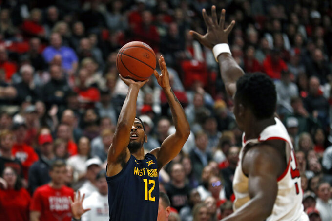 West Virginia's Taz Sherman (12) shoots the ball over Texas Tech's Russel Tchewa (54) during the first half of an NCAA college basketball game against Texas Tech, Wednesday, Jan. 29, 2020, in Lubbock, Texas. (AP Photo/Brad Tollefson)