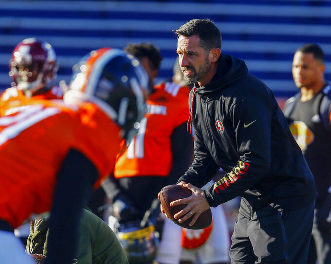 FILE - In this Thursday, Jan. 24, 2019, file photo, South head coach Kyle Shanahan of the San Francisco 49ers takes a snap during practice for the Senior Bowl college football game, in Mobile, Ala. Shanahan knows his 49ers NFL football team can go in one of two directions with the No. 2 overall pick in the draft. Take the top available pass rusher to help upgrade a defense that struggled to create takeaways a year earlier or move down in the draft and accumulate additional draft picks. (AP Photo/Butch Dill, File)