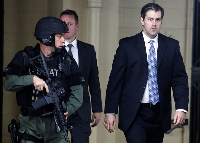 FILE- In this Dec. 5, 2016 file photo, Michael Slager, at right, walks from the Charleston County Courthouse under the protection from the Charleston County Sheriff's Department after a mistrial was declared for his trial in Charleston, S.C. Slager, a former South Carolina police officer serving 20 years in prison for killing an unarmed Black man who was running away from a traffic stop, said his lawyer never told him about a plea offer from prosecutors that could have cut years off his sentence. He is requesting a new sentence in federal court this week. (AP Photo/Mic Smith, File)