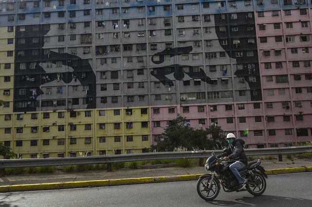 A biker wearing a protective face mask rides past a mural depicts