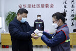 FILE - In this Feb. 10, 2020, file photo, released by Xinhua News Agency, Chinese President Xi Jinping, left, wearing a protective face mask, receives a temperature check at a community health center in Beijing. China's ruling Communist Party faces a politically fraught decision: Admit a viral outbreak isn't under control and cancel this year's highest-profile official event. Or bring 3,000 legislators to Beijing next month and risk fueling public anger at the government's handling of the disease. The party was already facing criticism of its heavy-handed censorship, on display during the outbreak, and other social controls under President Xi. (Pang Xinglei/Xinhua via AP, File)