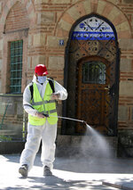 A Municipality worker disinfects the courtyard of historical Haci Bayram Mosque, in Ankara, Turkey, Thursday, May 28, 2020. Turkish authorities prepare mosques for communal prayers at limited capacity, observing social distancing rules, starting with Friday prayers since mosques shut down back in March; worshippers supposed to pray outside in mosque courtyards.( AP Photo/Ali Unal)