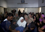 Relatives of Hamas security forces member, Mahmoud al-Adham, 28, mourn over his body during his funeral inside his home, in the town of Jabaliya, northern Gaza Strip, Thursday, July 11, 2019. Hamas' armed wing said Thursday that Israeli the army