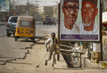 A young boy scavenges for re-sellable items from garbage on the streets, runs past a sign showing incumbent President Muhammadu Buhari, left, and local party official Mustapha Dankadai, right, in Kano, northern Nigeria Friday, Feb. 15, 2019. Nigeria is due to hold general elections on Saturday, pitting incumbent President Muhammadu Buhari against leading opposition presidential candidate Atiku Abubakar. (AP Photo/Ben Curtis)