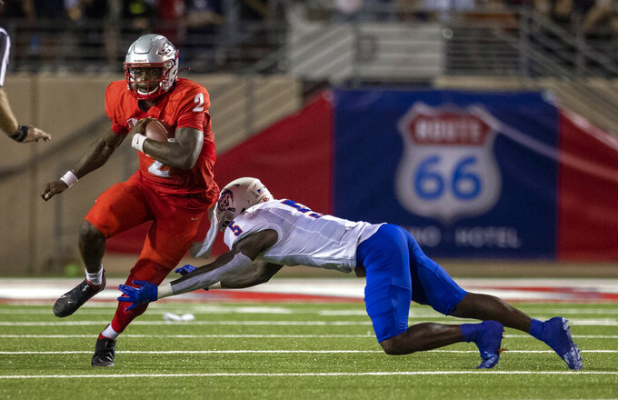 New Mexico quarterback Terry Wilson, left, avoids the tackle of Houston Baptist cornerback Coi Miller (5) during the second half of an NCAA college football game on Thursday, Sept. 2, 2021, in Albuquerque, N.M. (AP Photo/Andres Leighton)