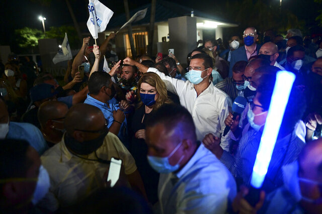 Pedro Pierluisi, gubernatorial candidate with the New Progressive Party (PNP), arrives at Vivo Beach Club accompanied by resident commissioner Jennifer Gonzalez to celebrate a slim lead of the pro-statehood party in the Puerto Rican general elections, in Carolina, Puerto Rico, Tuesday, Nov. 3, 2020. Pierluisi briefly served as governor following last year's massive protests that led to the resignation of former Gov. Ricardo Rosselló. (AP Photo/Carlos Giusti)