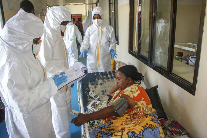 Doctors tend to a patient suffering from COVID-19 and receiving oxygen, in a ward for coronavirus patients at the Martini hospital in Mogadishu, Somalia Wednesday, Feb. 24, 2021. (AP Photo/Farah Abdi Warsameh)