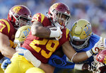 Southern California running back Vavae Malepeai (29) is tackled by UCLA defensive lineman Osa Odighizuwa, top right, during the first half of an NCAA college football game Saturday, Nov. 17, 2018, in Pasadena, Calif. (AP Photo/Marcio Jose Sanchez)