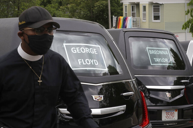 Rev. James Harrison, of the Southern Baptist Church, in Boston, walks Sunday, June 7, 2020 walks past hearses meant to honor fallen George Floyd, Breonna Taylor, and Ahmaud Arbery, before the start of a procession through Boston. The procession and a number of protests were triggered by the death of George Floyd who died on May 25 as a Minneapolis police officer pressed his knee into his neck, ignoring his cries and bystander shouts until he eventually stopped moving. (AP Photo/Steven Senne)