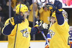 Nashville Predators right wing Craig Smith, left, celebrates with Rocco Grimaldi, right, after scoringhis third goal of an NHL hockey game against the New York Islanders in the second period Thursday, Feb. 13, 2020, in Nashville, Tenn. (AP Photo/Mark Humphrey)