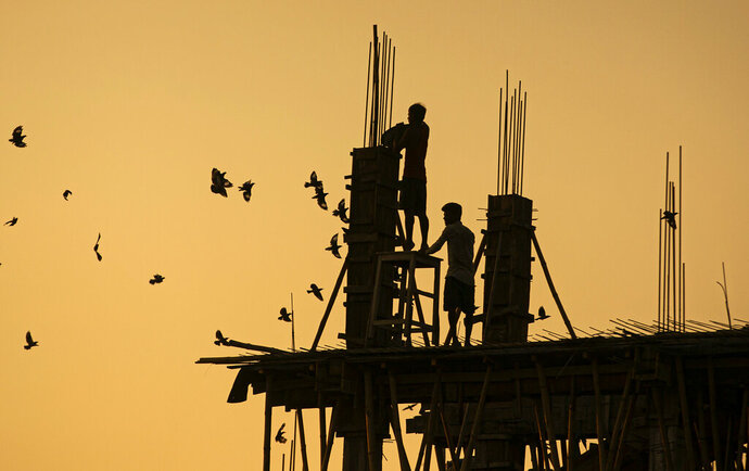 Indian laborers work at a building construction site in Gauhati, India, Monday, Oct. 19, 2020. (AP Photo/Anupam Nath)