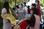 Parents wearing masks to curb the spread of the coronavirus wait in the shade as their children take part in their college entrance exams in Beijing, China on Tuesday, July 7, 2020. Almost 11 million students began taking China's university entrance exam Tuesday after a delay as the country worked to bring down coronavirus infections. (AP Photo/Ng Han Guan)