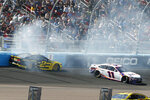 Brad Keselowski (2) and Denny Hamlin (11) crash during lap 65 of a NASCAR Cup Series auto race at Phoenix Raceway, Sunday, March 8, 2020, in Avondale, Ariz. (AP Photo/Ralph Freso)