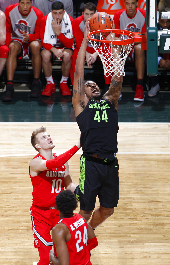 Michigan State's Nick Ward (44) goes up for a dunk against Ohio State's Justin Ahrens (10) and Andre Wesson (24) during the first half of an NCAA college basketball game, Sunday, Feb. 17, 2019, in East Lansing, Mich. (AP Photo/Al Goldis)