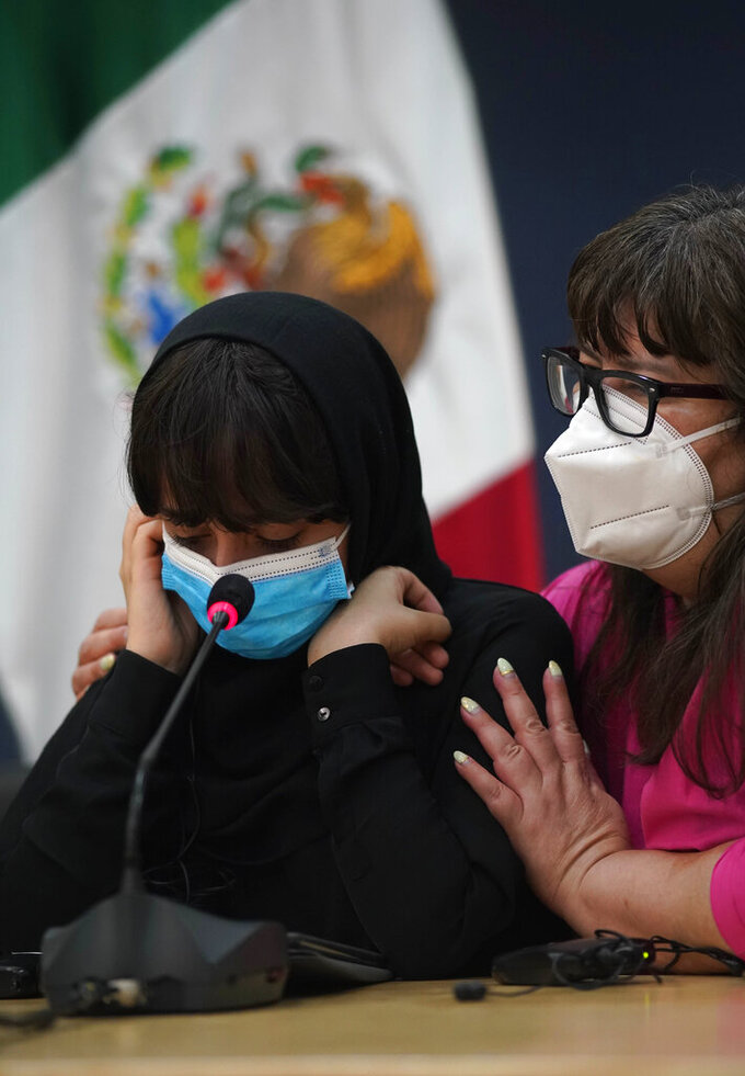 One of the original members of the Afghan all-girls robotics team, who have received threats from the Taliban, is comforted by a woman during a press conference after arriving to the Benito Juarez International Airport in Mexico City, Tuesday, Aug. 24, 2021. After extensive international efforts and coordination from a diverse group of volunteers to evacuate the team, the girls are now begging the international community to help get their family to safety with them. (AP Photo/Eduardo Verdugo)