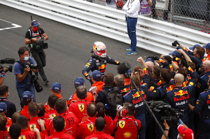 Red Bull driver Max Verstappen of the Netherlands, center, is congratulated by teammates after winning the Monaco Grand Prix at the Monaco racetrack, in Monaco, Sunday, May 23, 2021. (Gonzalo Fuentes, Pool via AP)
