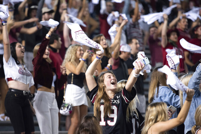 University of South Carolina students cheer before an NCAA college football game against Tennessee, Saturday, Sept. 26, 2020, in Columbia, S.C. Several parties and large gatherings coinciding with the University of South Carolina's football game had to be broken up Saturday, as people celebrated the first game of the season, police said. Columbia Police told The State newspaper Wednesday that three social distancing citations and four warnings were issued to residences that house some USC students. (AP Photo/Sean Rayford)