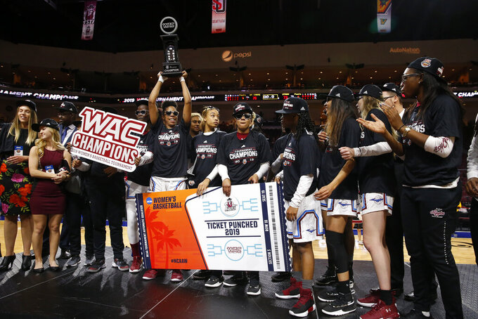 New Mexico State players pose with the trophy after defeating Texas-Rio Grande Valley 76-73 in double overtime during a NCAA college basketball Western Athletic Conference Women's Tournament championship game Saturday, March 16, 2019, in Las Vegas. (AP Photo/Steve Marcus)