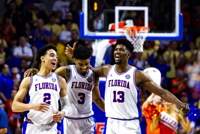Florida's Andrew Nembhard (2), Jalen Hudson (3) and Kevarrius Hayes (13) celebrate during during an NCAA college basketball game against Missouri, Saturday, Feb. 23, 2019. (Lauren Bacho/The Gainesville Sun via AP)