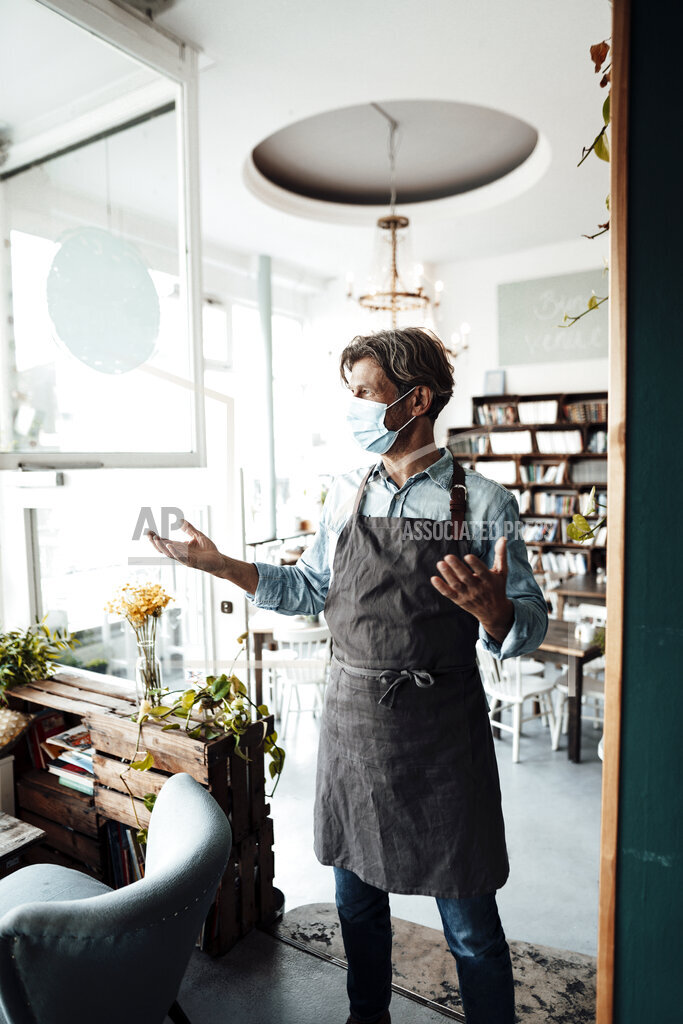 Male coffee shop owner gesturing while standing in cafe during COVID-19