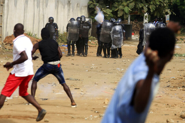 Demonstrator opposed to Ivory Coast President Alassane Ouattara running for a third term confront riot police in Abidjan Thursday Aug. 13, 2020. Ouattara announced earlier that he had accepted the ruling party's nomination and will run for a third presidential term in Octobre. (AP Photo/Diomande Ble Blonde)