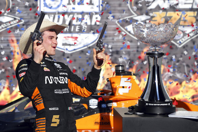 Pato O'Ward holds a pair of pistols as he celebrates his victory at an IndyCar Series auto race at Texas Motor Speedway on Sunday, May 2, 2021, in Fort Worth, Texas. (AP Photo/Richard W. Rodriguez)