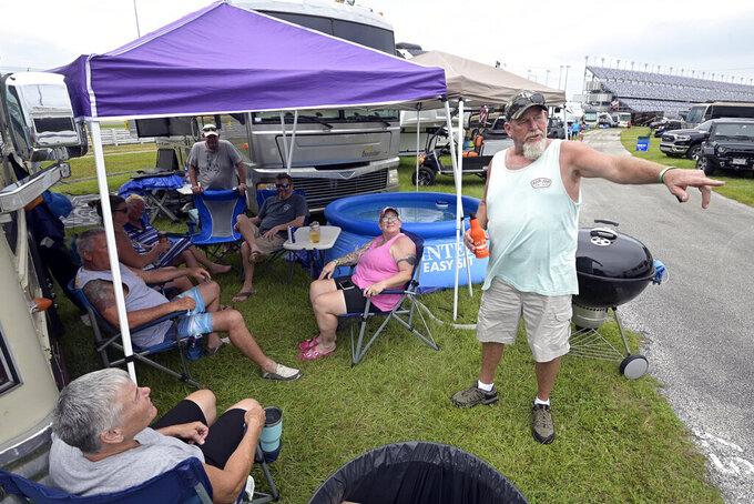 Race fans relax in the infield waiting for the evening start of a NASCAR Xfinity Series auto race at Daytona International Speedway, Friday, Aug. 27, 2021, in Daytona Beach, Fla. (AP Photo/Phelan M. Ebenhack)