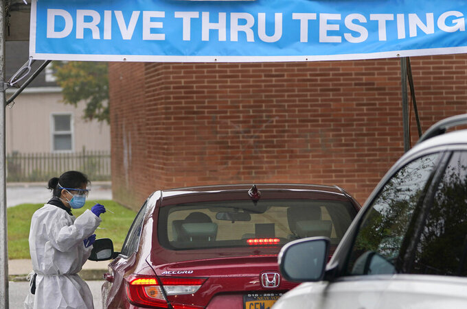 FILE - In this Wednesday Oct. 21, 2020, file photo a health worker prepares to administer a COVID-19 swab at a drive-thru testing site in Lawrence, N.Y. The the state Department of Health said a tiny fraction of vaccinated New Yorkers have tested positive for COVID-19. (AP Photo/Seth Wenig, File)