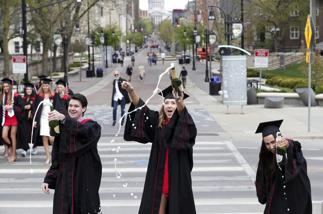 University of Wisconsin-Madison graduates, from left, Jacob Tottleben, of St. Louis, Lindsey Fischer, of La Crosse, and Olivia Gonzalez, of Milwaukee, open bottles of champagne at the State and Park Street crosswalk to celebrate after watching their virtual spring commencement ceremony on the rooftop of Fischer's apartment, on campus in Madison, Wis., Saturday, May 9, 2020. (Amber Arnold/Wisconsin State Journal via AP)