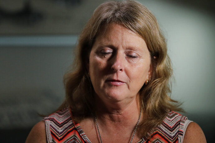 Debbi Hixon, pauses for a moment as she cries during an interview with The Associated Press on Friday, Feb. 14, 2020, in Hollywood, Fla. Hixon is the widow of Chris Hixon who was killed in a school shooting on Valentine's Day two years ago at Marjory Stoneman Douglas High School. She recently had the family home renovated by the program
