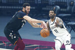 Cleveland Cavaliers' Larry Nance Jr. (22) steals a pass intended for Brooklyn Nets' Kyrie Irving (11) during the first half of an NBA basketball game, Wednesday, Jan. 20, 2021, in Cleveland. (AP Photo/Tony Dejak)